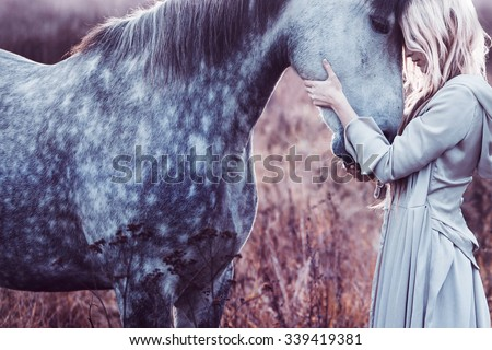beauty blondie with horse in the field,  effect of toning - stock photo
