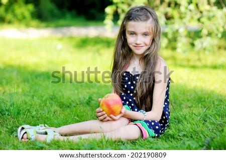 Beauty brunette kid girl eating apple outdoors in the summer day - stock photo