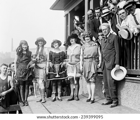 1921 beauty contestants at Washington, D.C. beach wear soon to be out of fashion bathing suits with shoes and stockings.