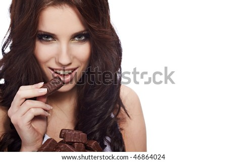 beauty portrait of a cute brunette girl in act to eat a chocolate candy - stock photo
