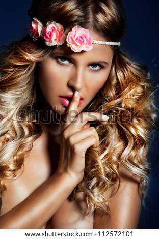 Beauty portrait of Young, blond, lady with long, silky hair. Woman with a Blue eyes ,Pink lipstick and flowers on her head posing on a blue background .Hush babe. - stock photo