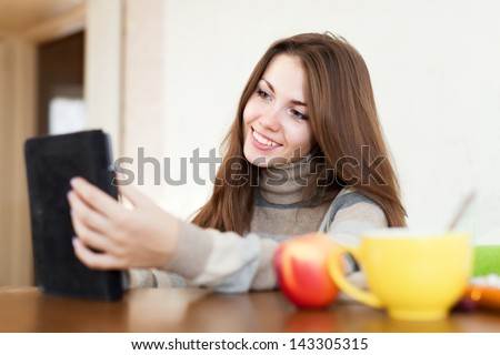 beauty woman reads e-book in home interior - stock photo