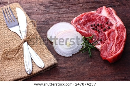 beef on wooden table with cutlery  - stock photo