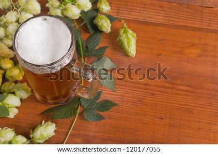 beer and hop on a wooden background - stock photo