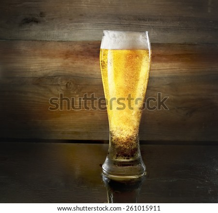 Beer glass on old wooden background - stock photo