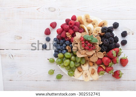 Berries, fruit and muesli Ingredients for healthy breakfast on white wooden table, close-up top view horizontal. Macro shot selective focus - stock photo