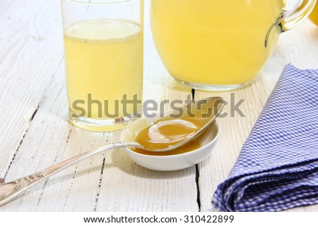 Beverage of honey and lemon in a glass, spoon with honey