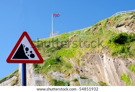 'Beware falling rocks' sign with steep cliffs in the background - stock photo