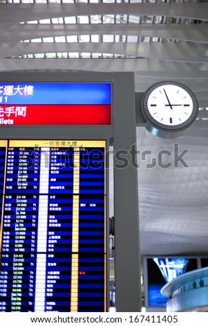 Big airport clock close to arrival board in airport terminal. Travel concept. - stock photo