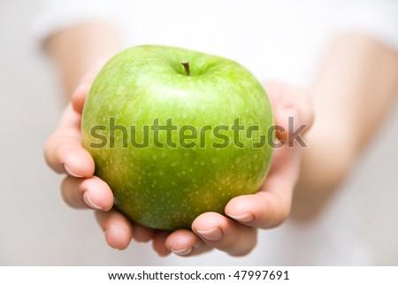 big green apple in beautiful female hands - stock photo