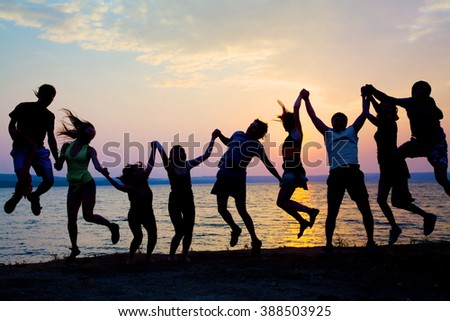 big group of happy young people dancing at the beach on  beautiful summer sunset - stock photo
