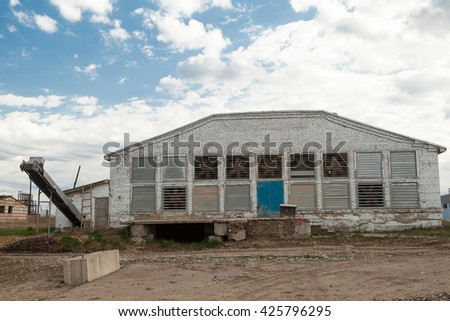 big white Poultry Farm hen house in a cloudy day dirty road - stock photo