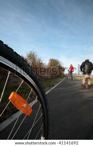 Biking (the image is motion blurred to convey movement; focus is on the wheel, the female biker and the old man are left out of focus) - stock photo
