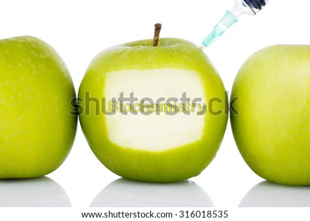 """Biochemistry"" text on green apple with syringe injected on it isolated white background - concept for genetically modified foods for diet,future health, science, chemistry, medicine and people.  - stock photo"