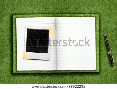 Biography,curriculum vitae concept, blank opened book and empty photo on the green grassland and pen - stock photo