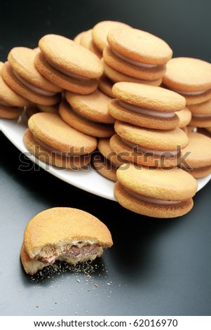 Biscuits. Sweet sandwich-biscuits filled with hazelnut cream arranged in a pyramid on a white plate with one bitten on dark background - stock photo