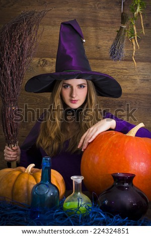 bitch blonde witch with a broom and pumpkins for Halloween