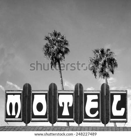 black and white aged and worn vintage photo of motel sign with palm trees                            - stock photo