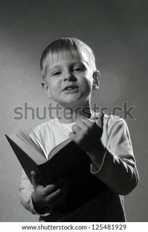 black and white portrait of cute little boy with book - stock photo