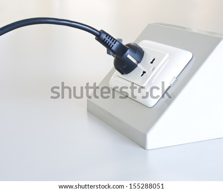 black male plug connecting in electrical outlet - stock photo