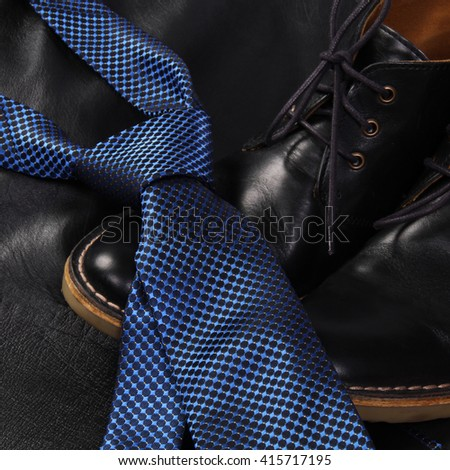 Black men's shoes and blue luxury tie on dark background. - stock photo