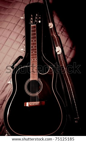 black shiny acoustic guitar  in case - stock photo