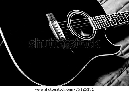black shiny acoustic guitar  on bed - stock photo