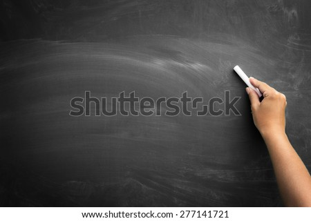 Blank blackboard / chalkboard, hand writing on black chalk board holding chalk, great texture for text. - stock photo