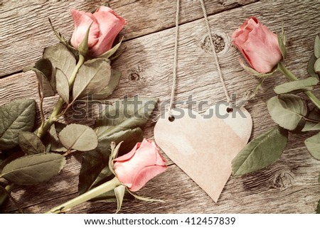 Blank heart shaped tag and three roses on wooden background.