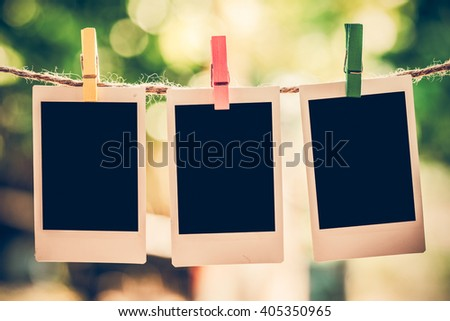 3 Blank instant photo and clippaper hanging on the clothesline with bokeh nature background.Designer concept.Vintage or retro tone. - stock photo