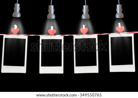 4 Blank instant photo and red clip paper heart hanging on the clothesline with black background in room with ceiling lamp.Designer concept. - stock photo