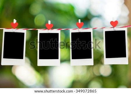 4 Blank instant photo and red clip paper heart hanging on the clothesline with nature bokeh background..Designer concept. - stock photo