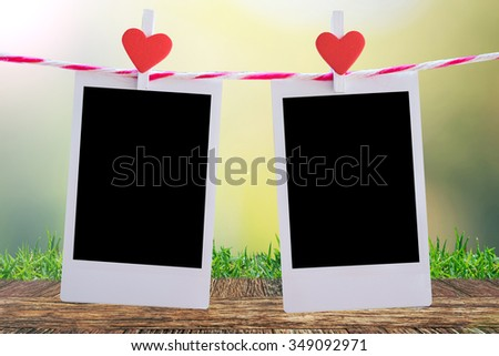 2 Blank instant photo and red clip paper heart hanging on the clothesline with wooden table floor and grass natural bokeh background..Designer concept. - stock photo