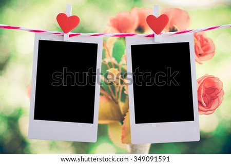2 Blank instant photo and red clippaper heart hanging on the clothesline with pink rose flower background. vintage tone.Designer concept. - stock photo