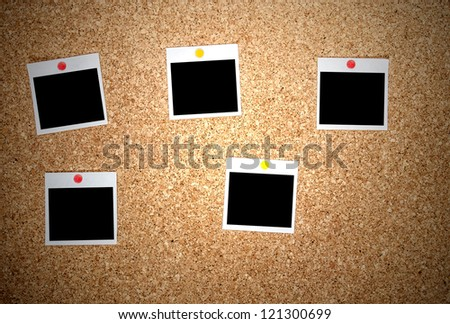 Blank instant photos pinned to a cork board with clipping path - stock photo
