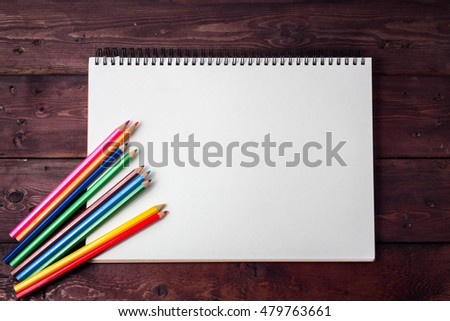 blank paper and colorful pencils on old wooden table with copy space school concept