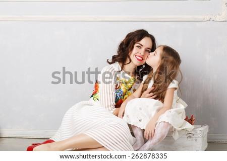 blond little girl kissing her mother - stock photo