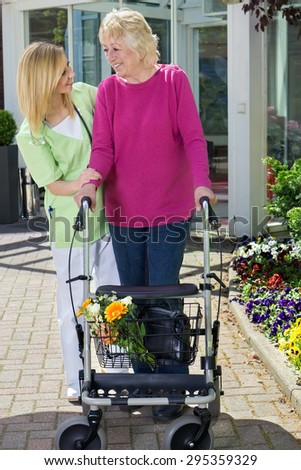 Blond Smiling Nurse Holding Arm of Senior Woman with Walker  Helping Senior Resident to Walk Outdoors in front of Building Entrance Near Flower Beds and Showing Care and Concern. - stock photo