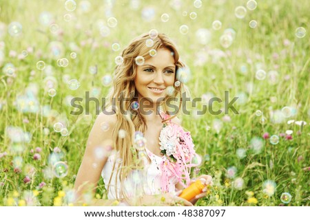 Blonde starts soap bubbles - stock photo