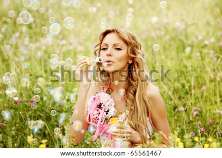 Blonde starts soap bubbles in a green field - stock photo