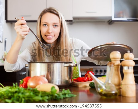 Blonde woman cooking   soup in home kitchen