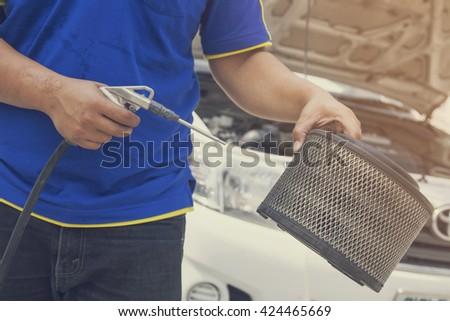 Blowing car air filter - stock photo