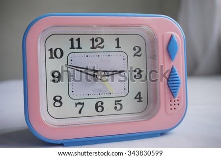 Blue alarm clock on white background.Selective focus - stock photo