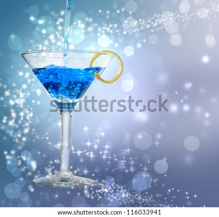 Blue cocktail being poured into a glass on abstract lights background - stock photo