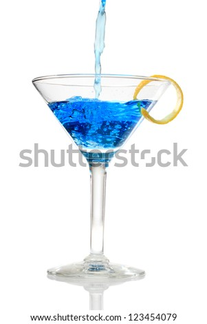 Blue cocktail being poured into a glass on white background - stock photo