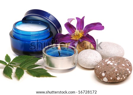 blue cosmetic cream,pebbles, candle, flower on white