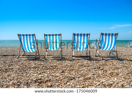 4 blue deck chairs on a pebble beach - stock photo