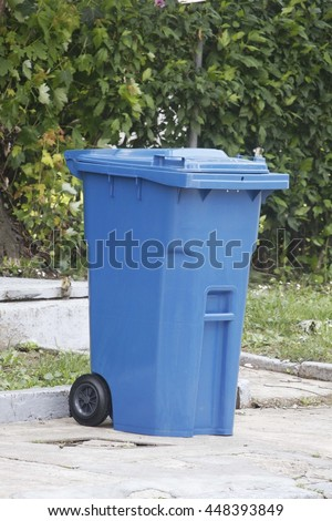 Blue plastic trash can - stock photo