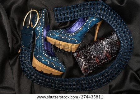 Blue shoes and belt, purse lying on black satin, as background - stock photo