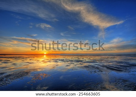 Blue skies over a bright ocean sunset with distant cliffs - stock photo